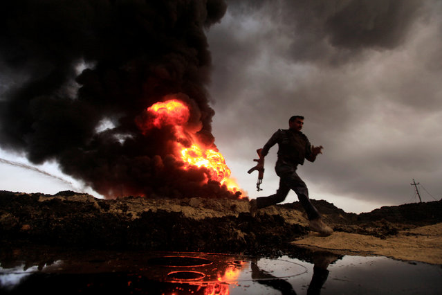 Flames and smoke rise from oil wells set ablaze by Islamic State militants before they fled the oil-producing region of Qayyara, Iraq, November 4, 2016. (Photo by Alaa Al-Marjani/Reuters)