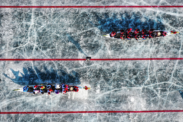 This aerial view shows teams competing during an ice dragon boat race on a frozen river in Shenyang, in northeastern China's Liaoning province on February 2, 2021. (Photo by AFP Photo/China Stringer Network)