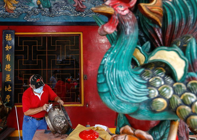 A man wearing a protective mask wipes a traditional incense urn ahead of the Chinese Lunar New Year celebration following the coronavirus disease (COVID-19) outbreak, at a temple in Jakarta, Indonesia, February 4, 2021. (Photo by Ajeng Dinar Ulfiana/Reuters)