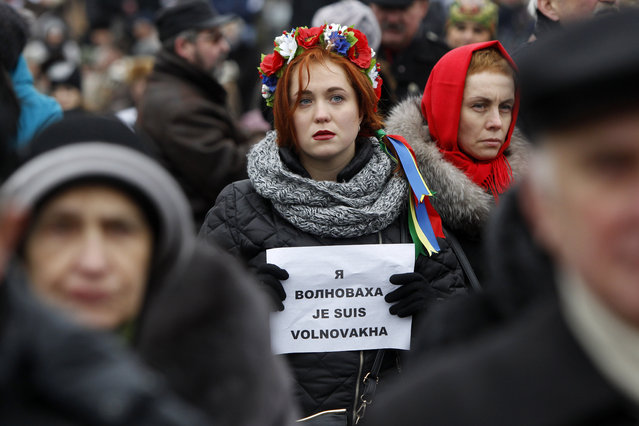 """People hold up signs reading """"I Am Volnovakha"""" during a rally at Independence Square in Kiev, Ukraine, in solidarity with the victims of a rocket attack this week that claimed 13 lives on a highway near the eastern town of Volnovakha, on Sunday, January 18, 2015. Ukraine's government accused Russian-backed separatists of launching the rocket attack, which hit a passenger bus, but the rebels have rejected that charge. (Photo by Sergei Chuzavkov/AP Photo)"""