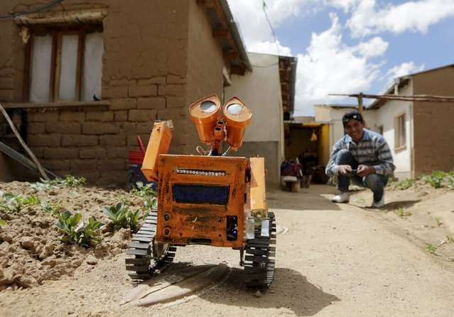 A replica of the Wall-E character is remotely controlled with a mobile phone by Bolivian student Esteban Quispe, 17, in Patacamaya, south of La Paz, December 10, 2015. (Photo by David Mercado/Reuters)