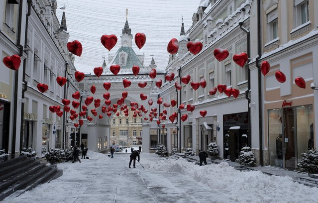Workers remove snow in a street, which is decorated ahead of Valentine's Day, following heavy snowfall in central Moscow, Russia on February 13, 2021. (Photo by Shamil Zhumatov/Reuters)