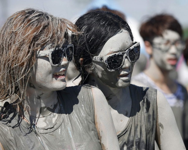 Tourists look at other festival-goers playing in the mud during the Boryeong Mud Festival at Daecheon beach in Boryeong, about 190 km (118 miles) southwest of Seoul, July 19, 2013. About 2 to 3 million domestic and international tourists visit the beach during the annual mud festival, according to the festival organisers. (Photo by Lee Jae-Won/Reuters)