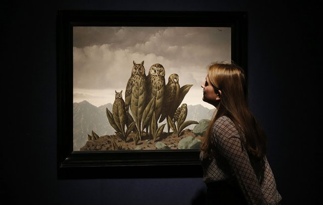 "A member of staff poses with ""Les compagnons de la peur"" by Rene Magritte at Christie's auction house in London, January 30, 2015. The Magritte is estimated to for between U.S. $4-5.3 million (2.7-3.5 million British pounds) when it is auctioned on Feb. 4 in London. (Photo by Suzanne Plunkett/Reuters)"