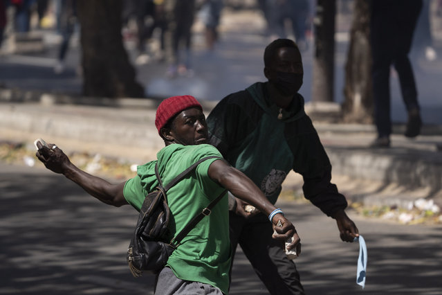 A demonstrators throws rocks at riot policemen during protests against the arrest of opposition leader and former presidential candidate Ousmane Sonko, Senegal, Monday, March 8, 2021. Senegalese authorities have freed opposition leader Ousmane Sonko while he awaits trial on charges of rape and making death threats. The case already has sparked deadly protests threatening to erode Senegal's reputation as one of West Africa's most stable democracies. That's because Sonko's supporters are accusing President Macky Sall of pursuing the criminal charges to derail the opposition figure's prospects in the upcoming 2024 election. (Photo by Leo Correa/AP Photo)