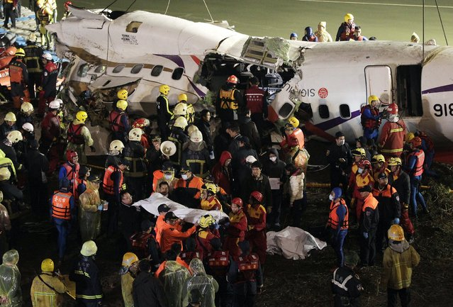 Rescuers remove a body in a bag after a TransAsia Airways plane crash landed in a river in New Taipei City, February 4, 2015. (Photo by Pichi Chuang/Reuters)