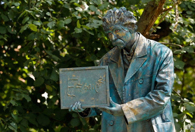 """An artist called """"Albert Eisntein"""" takes part in the festival """"Statues en Marche"""" in Marche-en-Famenne, Belgium, July 22, 2018. Living statues are a common sight in many city centres, but it is rare to see such a diverse range of this peculiar form of street art for which performers must keep still for painfully long periods of time to create the desired illusion. (Photo by Yves Herman/Reuters)"""