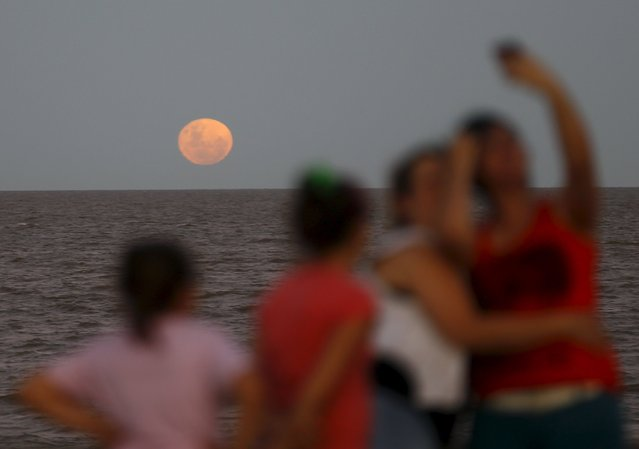 People take a selfie as a full moon rises over the Buenos Aires sky December 25, 2015. Its appearance marks the first full moon to happen on Christmas day since 1977, and this phenomenon will not happen again until 2034, according to weather reports. (Photo by Enrique Marcarian/Reuters)