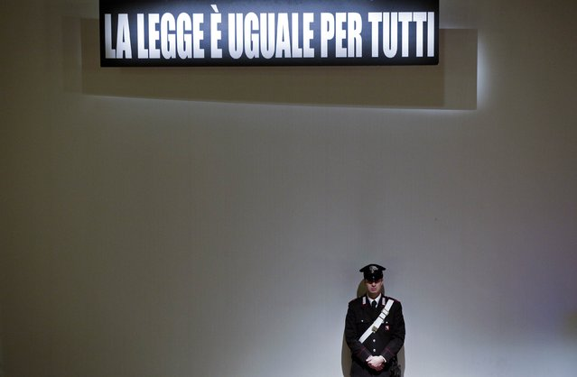 """A Carabiniere paramilitary policeman stands below a sign that reads, """"The law is equal for everyone"""", during the trial of the captain of the Costa Concordia cruise liner Francesco Schettino in Grosseto February 9, 2015. (Photo by Max Rossi/Reuters)"""