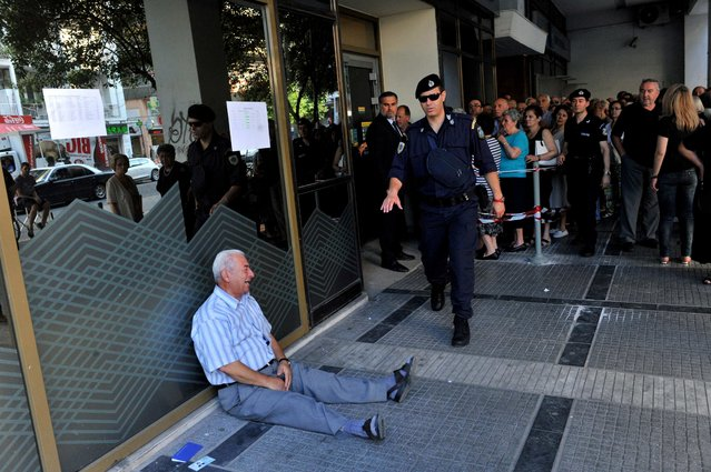 """An elderly man is crying outside a national bank branch as pensioners queue to get their pensions, with a limit of 120 euros, in Thessaloniki, Greece, July 3, 2015. Greece is almost evenly split over a crucial weekend referendum that could decide its financial fate, with a """"Yes"""" result possibly ahead by a whisker, the latest survey showed. (Photo by Sakis Mitrolidis/AFP Photo)"""