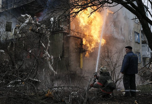 A firefighter works to extinguish a fire at a residential block, which was damaged by a recent shelling according to locals, on the outskirts of Donetsk, eastern Ukraine February 9, 2015. (Photo by Maxim Shemetov/Reuters)
