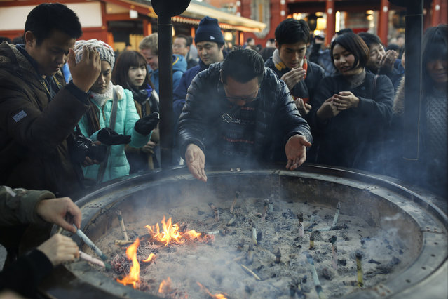 People bath in incense smoke at the Sensoji temple ahead of the New Year holidays in Tokyo, Japan December 30, 2015. (Photo by Thomas Peter/Reuters)