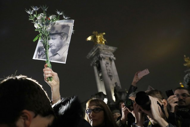 A woman holds flowers and a portrait during a ceremony in tribute to the Cuban revolutionary icon Fidel Castro, next to the statue of Simon Bolivar, on November 26, 2016 in Paris. (Photo by Patrick Kovarik/AFP Photo)