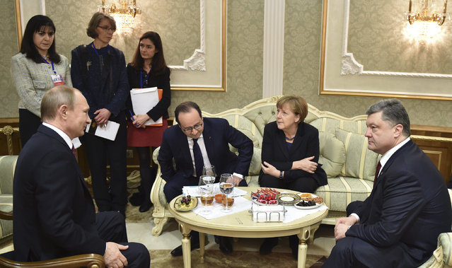 Left to right, Russian President Vladimir Putin,  French President Francois Hollande, German Chancellor Angela Merkel, and Ukrainian President Petro Poroshenko talk in Minsk, Belarus, Wednesday, February 11, 2015. (Photo by Mykola Lazarenko/AP Photo)