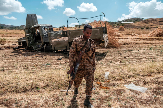 A member of the Ethiopian Defense Forces walks away from a damaged military truck abandoned on a road near the village of Ayasu Gebriel, East of the Ethiopian city of Alamata, on December 10, 2020. (Photo by Eduardo Soteras/AFP Photo)