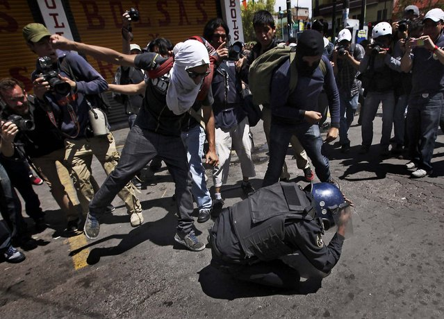 A policeman is beaten up by a group of protesters during a march in Mexico City, on September 1, 2013. The officer was later taken away by colleagues. Teachers, anarchists and other groups protested against proposed energy and education reforms. (Photo by Marco Ugarte/Associated Press)