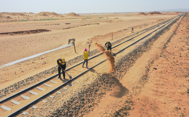 Aerial photo shows workers removing sand along Linhe-Ceke railway in north China's Inner Mongolia Autonomous Region, April 14, 2021. With a total length of 768 kilometers, the Linhe-Ceke railway is one of the important junctions connecting Mongolia and China. Two passenger trains and nearly 40 freight trains run on it every day. In order to control the sand damage, eleven sand control stations have been set up along the Linhe-Ceke railway that traverses more than 400 kilometers of desert. The railway sand control workers are stationed here all year round to prevent the accumulation of quicksand on the railway lines and ensure the smooth railway transportation. (Photo by Xinhua News Agency/Rex Features/Shutterstock)