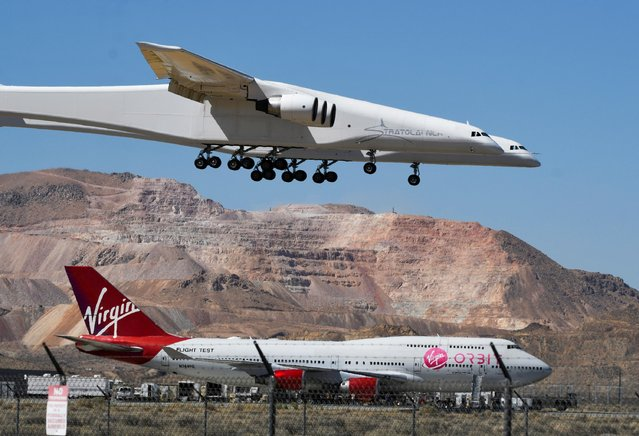 The Stratolaunch plane, the world's largest, comes in for a landing over Virgin Orbit 747 Cosmic Girl after it performed a 2nd test flight in Mojave, California, U.S., April 29, 2021. The plane, designed to transport hypersonic vehicles and facilitate easy access to space, made its second test flight, two years after its first voyage. (Photo by Gene Blevins/Reuters)