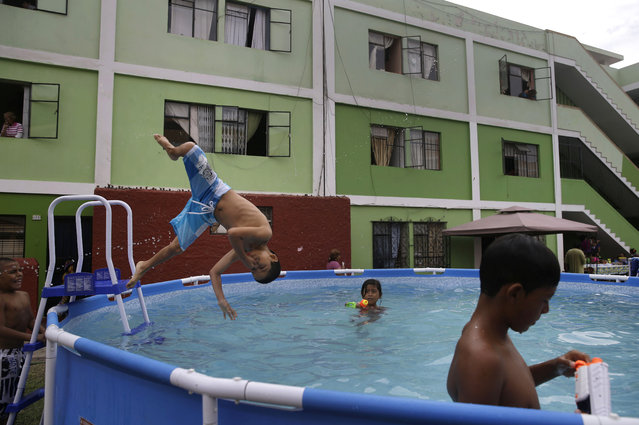In this Sunday, February 15, 2015 photo, a young boy dives into a pool head first, holding his nose, in Callao, Peru. While children frolic and adults lounge in the waters, municipal officials gripe about the waste in a desert city battling chronic water shortages. (Photo by Martin Mejia/AP Photo)