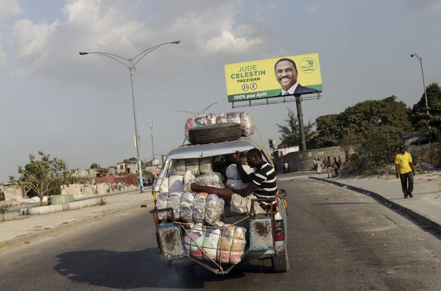 A man sits on the back of a tap-tap as it passes next to an electoral poster of presidential candidate Jude Celestin in Port-au-Prince, Haiti, January 15, 2016. Haiti's opposition presidential candidate Jude Celestin has announced he will not take part in a runoff election because he does not have faith in the process, in a move that could mean a shoe-in for the ruling party on Jan. 24. (Photo by Andres Martinez Casares/Reuters)