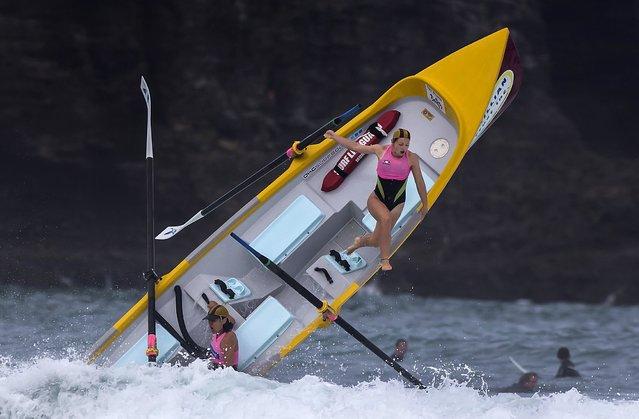 Alison Cragie (top), a member of a women's surf boat crew, is thrown from the boat by a breaking wave during a race in the Day of Giants Surf Boat Competition being held at Piha Beach, located west of Auckland February 21, 2015. (Photo by Peter Meecham/Reuters)
