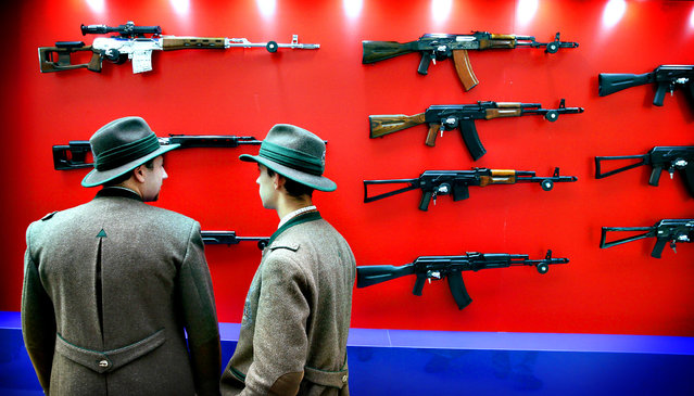 Visitors look at Kalashnikov automatic rifles during the Arms and Hunting Exhibition in Moscow, Russia, 10 October 2013. The exhibition that runs from 10 to 13 October 2013. (Photo by Yuri Kochetkov/EPA)