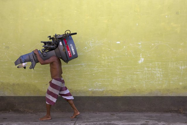 A man carries an outboard motor which he found and recovered from the seabed in Rio Caribe, a town near caribbean islands, in the eastern state of Sucre, Venezuela October 29, 2015. Driven by a deepening economic crisis, smuggling across Venezuela's land and maritime borders – as well as illicit domestic trading – has accelerated to unprecedented levels and is transforming society. Although smuggling has a centuries-old history here, the socialist government's generous subsidies and a currency collapse have given it a dramatic new impetus. (Photo by Carlos Garcia Rawlins/Reuters)