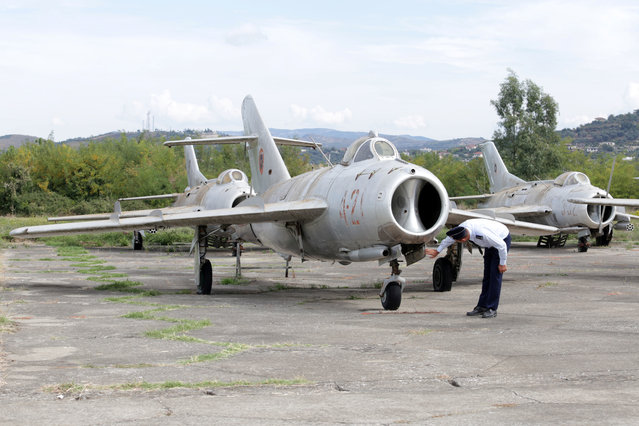 """An Albanian Air Force crew member inspects a MiG-17 jet fighter in Kucova Air Base in Kucova, Albania on October 3, 2018. """"The base is the first footprint of NATO in the Western Balkans as it will transform Kucova into the first NATO air base for the region,"""" Defence Minister Olta Xhacka told Reuters. NATO will spend over 50 million euros ($58 million) on the first stage of work to turn Kucova into a support base for supplies, logistics, training and drills, Xhacka said. (Photo by Florion Goga/Reuters)"""