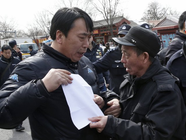 A plain clothed policeman (L) confiscates a paper bearing a slogan from a family member of passengers onboard the missing Malaysia Airlines flight MH370, outside Yonghegong Lama Temple after a gathering of family members of the missing passengers in Beijing March 8, 2015. Prime Minister Najib Razak said on Sunday Malaysia remains committed to the search for the missing MH370 jetliner a year after it vanished without trace and he is hopeful it will be found.