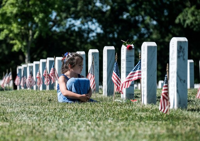 A girl sits in front of a headstone during Memorial Day as visitors honor veterans and those lost in war at Arlington National Cemetery, Virginia, U.S., May 31, 2021. (Photo by Michael A. McCoy/Reuters)