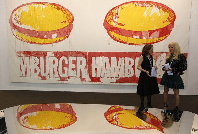 "People talk in front of ""Double Hamburger"" by U.S. artist Andy Warhol, reflected on another installation, at Art Basel's 2015 edition in Hong Kong March 13, 2015. (Photo by Bobby Yip/Reuters)"