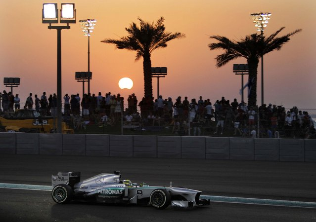 As the moon crosses in front of the sun during the partial solar eclipse, Mercedes driver Nico Rosberg of Germany steers his car during the Abu Dhabi Formula One Grand Prix at the Yas Marina racetrack in Abu Dhabi, United Arab Emirates. (Photo by Kamran Jebreili/Associated Press)