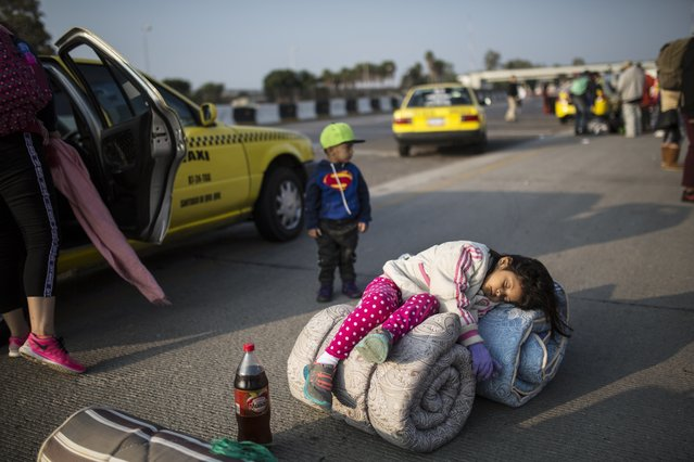 Central American migrant Sofia Hernandez, 5, part of the caravan hoping to reach the U.S. border, sleeps while her family tries to get a ride on a truck, in Celaya, Mexico, Sunday, November 11, 2018. (Photo by Rodrigo Abd/AP Photo)