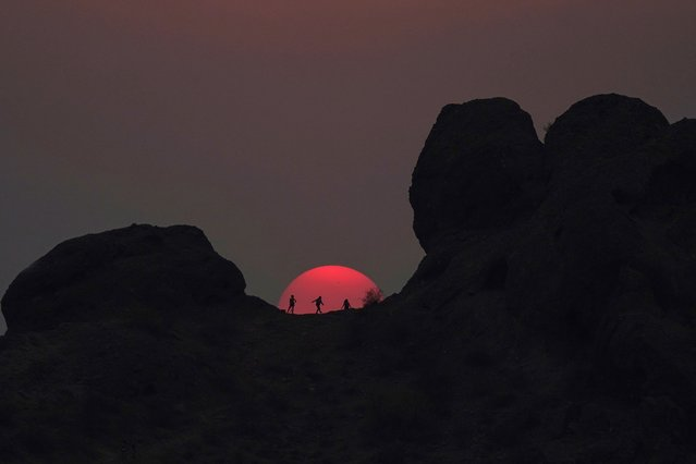 Hikers pause to watch the sunset at Papago Park during a heatwave where temperatures reached 115-degrees Tuesday, June 15, 2021, in Phoenix. (Photo by Ross D. Franklin/AP Photo)