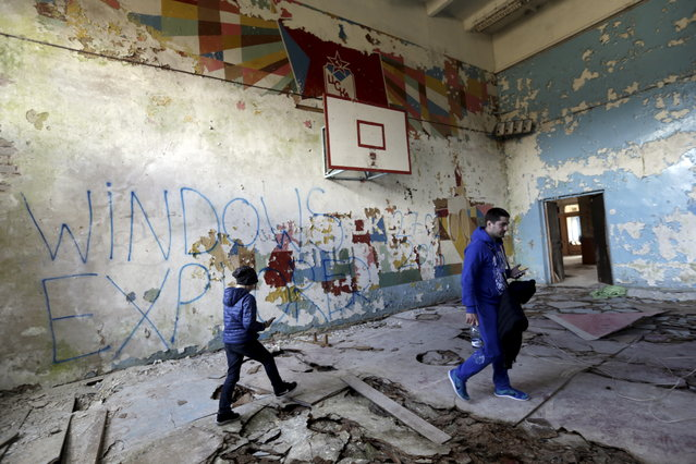 LATVIA: People walk inside abandoned sports hall in the ghost town of a former Soviet military radar station near Skrunda, Latvia, April 9, 2016. (Photo by Ints Kalnins/Reuters)