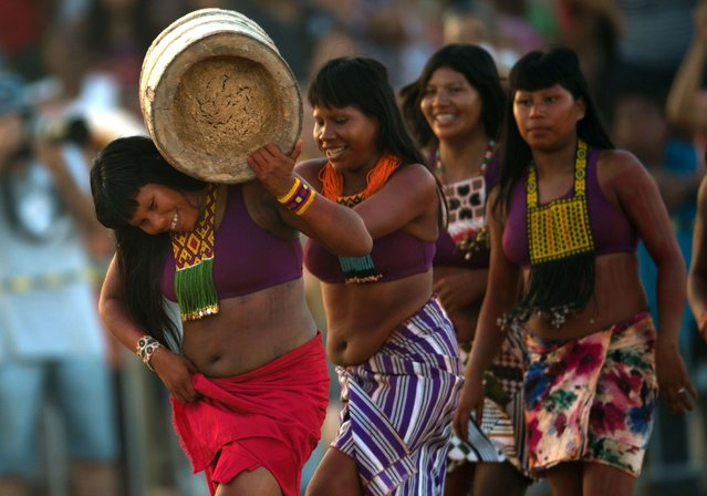 "Brazilian indigenous women from the Kraho ethnic group take part in the ""Corrida de Tora"" (race with a trunk), during the first day of the International Games of Indigenous Peoples, in Cuiaba, state of Mato Grosso, on November 10, 2013. 1500 natives from 49 Brazilian ethnic groups and from another 17 countries are gathering in Cuiaba until November 16 to compete in some 30 athletic disciplines, many of their own. (Photo by Christophe Simon/AFP Photo)"