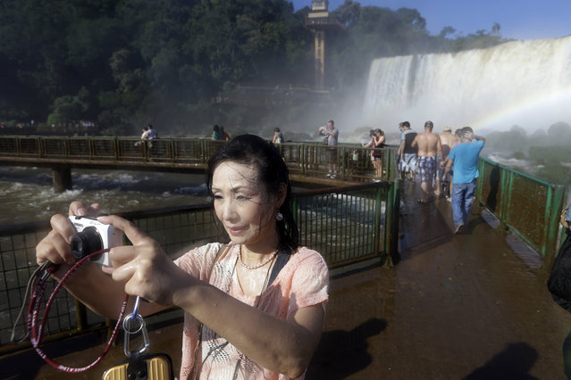 "In this March 14, 2015 photo, Japanese tourist Hiromi Kanetake takes picturess as she stands in the spray of Iguazu Falls in Brazil. Kanetake summed up her feelings during her visit: ""I'm so excited that my tears are mixing with the river water that floats in the air. I'm very happy that I came from so far away with my son Takayuki to see this"". (Photo by Jorge Saenz/AP Photo)"