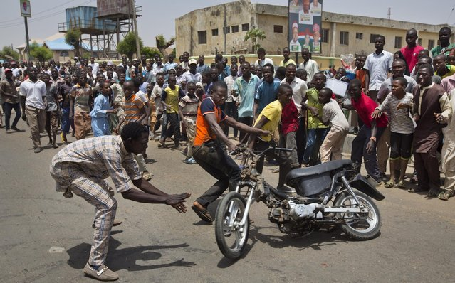 Supporters of opposition candidate Gen. Muhammadu Buhari's All Progressives Congress (APC) party celebrate by wheel-spinning motorcycles what they said was the senatorial win in Kano Central district of APC candidate Rabiu Musa Kwankwaso, in Kano, northern Nigeria Monday, March 30, 2015. Nigerians are waiting in hope and fear for results of the most tightly contested presidential election in the nation's turbulent history. (Photo by Ben Curtis/AP Photo)