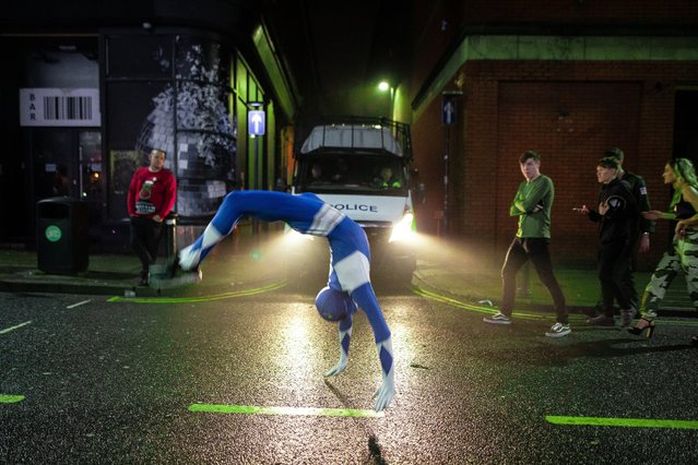 A man in fancy dress performs summersaults on King Street, Wigan, UK on December 27, 2018. Revellers in Wigan enjoy Boxing Day drinks and clubbing in Wigan Wallgate. In recent years a tradition has been established in which people go out wearing fancy-dress costumes on Boxing Day night. (Photo by Joel Goodman/London News Pictures)
