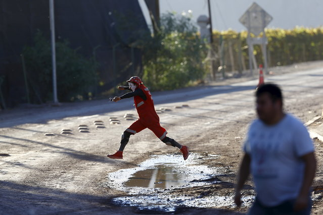 A volunteer dressed as a clown jumps over a puddle in a street of  San Antonio town, April 7, 2015. (Photo by Ivan Alvarado/Reuters)