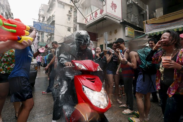 Revellers splash water onto passing motorists during Songkran Festival celebrations at Kowloon City district is known as Little Thailand as there is large number of restaurants and shops run by Thais April 12, 2015. (Photo by Tyrone Siu/Reuters)