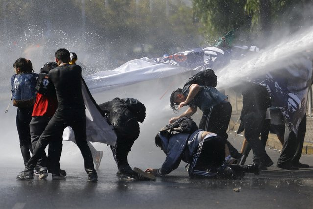 Protesters are hit by a jet of water released from a riot police vehicle during a demonstration against the government to demand changes in the education system at Santiago, April 16, 2015. (Photo by Ivan Alvarado/Reuters)