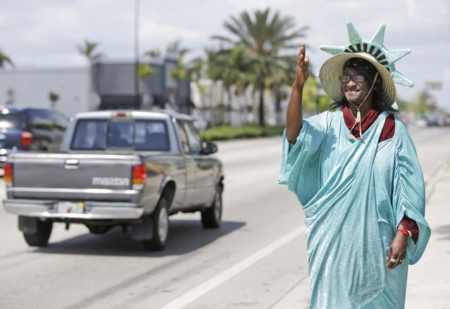 Dressed as Lady Liberty, Wendy James, of Lauderhill, Fla., waves to passing motorists outside a Liberty Tax Service office on the deadline day for U.S. Income Tax filing Wednesday, April 15, 2015, in Hallandale Beach, Fla. (Photo by Wilfredo Lee/AP Photo)