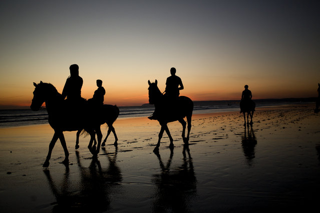 Tourists ride horses along the beach as the sun sets in Cadiz the south of Spain, Wednesday, April 1, 2015.  (Photo by Emilio Morenatti/AP Photo)