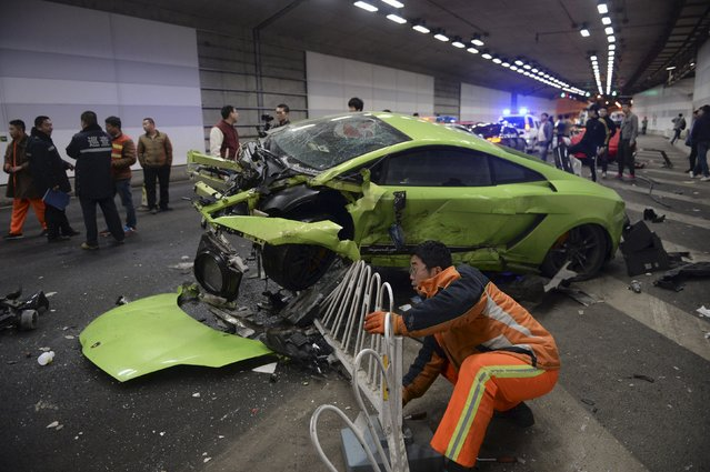 A rescuer tries to remove a part of a broken fence below a damaged Lamborghini after it collided with a Ferrari inside a tunnel in Beijing, April 12, 2015. One passenger was injured during the incident, while policemen are looking into the cause. Residents nearby said the tunnel is a common spot for illegal car racing in Beijing, local media reported. (Photo by Reuters/Stringer)