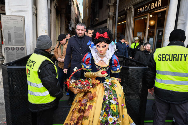 Security officers check revellers wearing masks and period costumes accessing Piazza San Marco (Saint Mark's Square) during the Venice Carnival on February 23, 2019 in Venice, Italy. (Photo by Alberto Pizzoli/AFP Photo)
