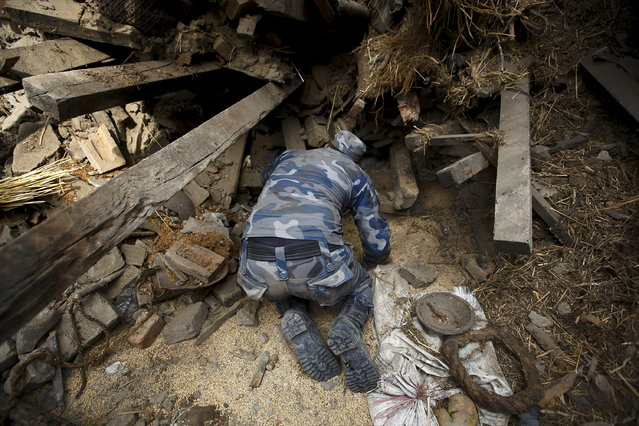 Rescue team member works to dig out the trapped body of a woman from a collapsed house a day after an earthquake in Bhaktapur, Nepal April 26, 2015. (Photo by Navesh Chitrakar/Reuters)