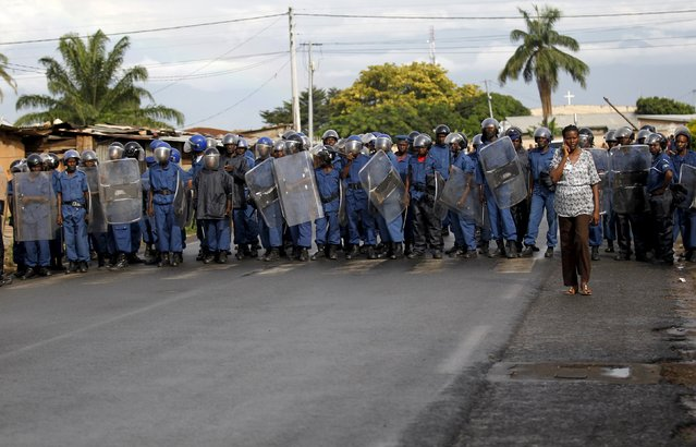 A woman walks past riot police during street protests against the decision made by Burundi's ruling National Council for the Defence of Democracy-Forces for the Defence of Democracy (CNDD-FDD) party to allow President Pierre Nkurunziza to run for a third five-year term in office, in the capital Bujumbura, April 26, 2015. (Photo by Thomas Mukoya/Reuters)