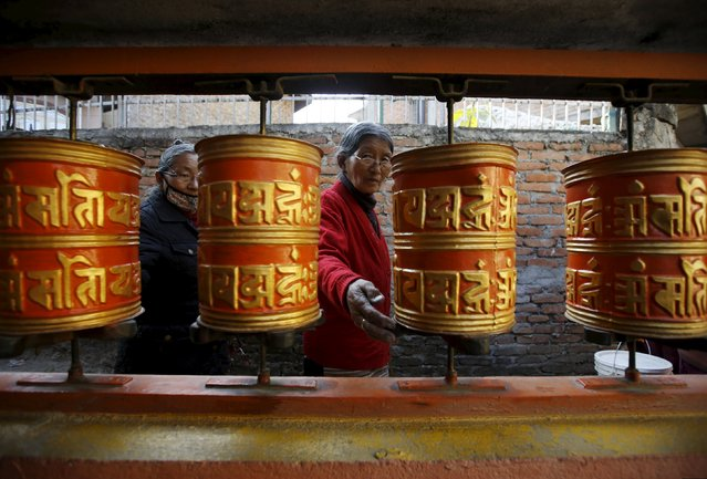 Tibetan women spin prayer wheels at the Tibetan Refugee camp in Lalitpur, Nepal, March 10, 2016. Tibetans mark March 10 as their uprising day. (Photo by Navesh Chitrakar/Reuters)