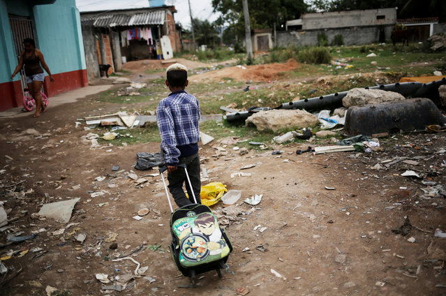 A boy pulls his school bag at a favela, or a slum, in Rio de Janeiro, Brazil June 24, 2016. (Photo by Nacho Doce/Reuters)